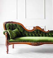 A green couch with a wood frame inside a white room