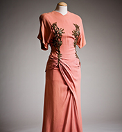 A pink dress on a mannequin, it's a coral color with gold designs on the sides